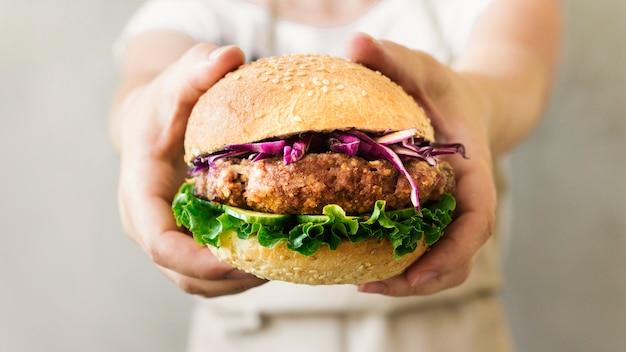 Primer plano cocinero sosteniendo hamburguesa en manos