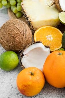 Primer plano de coco fresco con naranjas y piña
