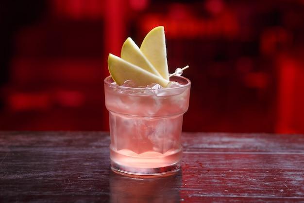 Primer plano de un cóctel fitzgerald en vaso corto, ginebra, de pie sobre la barra del bar, aislado en un espacio de luz roja.