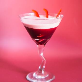 Primer plano de un cóctel fresco en vaso de martini sobre fondo rosa