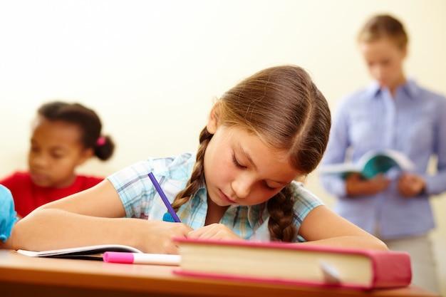 Primer plano de colegiala sosteniendo un lápiz morado