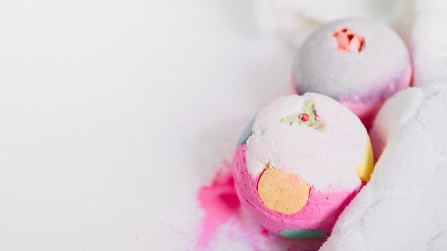 Primer plano de coloridas bombas de baño y servilleta sobre fondo blanco