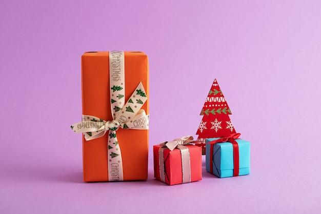 Primer plano de coloridas cajas de regalo y un árbol de navidad de papel en el fondo púrpura