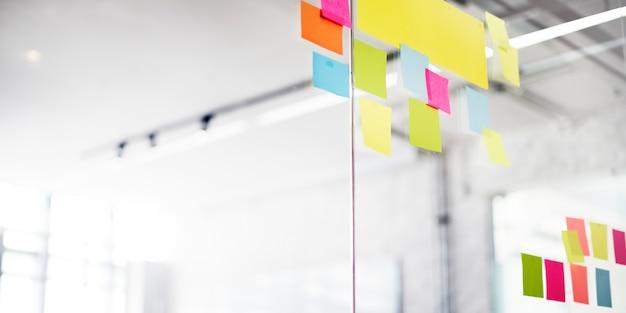 Primer plano de coloridas notas adhesivas en blanco sobre el vidrio de la oficina