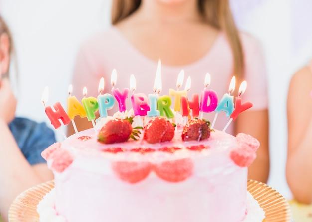 Primer plano de coloridas velas de cumpleaños que brillan intensamente en la torta de relleno de fresa
