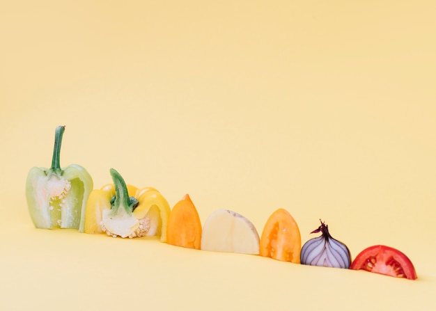 Primer plano de coloridas verduras crudas en superficie amarilla