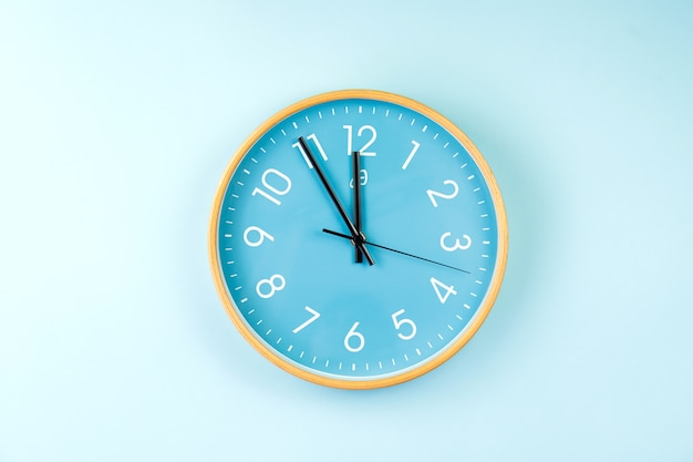 Primer plano de un colorido reloj de pared sobre fondo azul. imagen minimalista plana de reloj de pared de plástico.