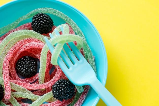 Primer plano de coloridos gusanos de gelatina se muestra como espagueti