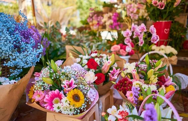 Primer plano de coloridos ramos de flores en contenedores en una tienda al aire libre