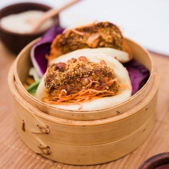 Primer plano de comida tradicional gua bao en vapor de bambú