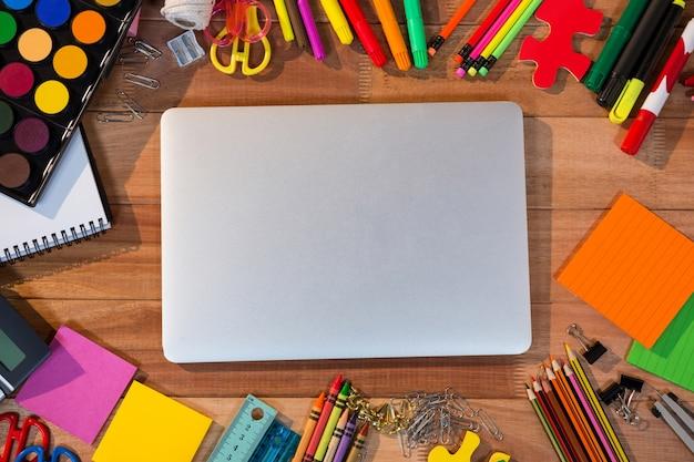 Primer plano de la computadora portátil con diversos artículos de papelería