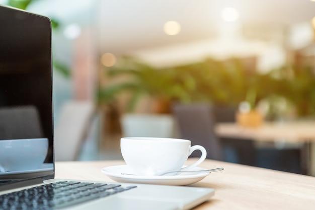 Primer plano de la computadora portátil de negocios y la taza de café en la mesa de madera en la cafetería.