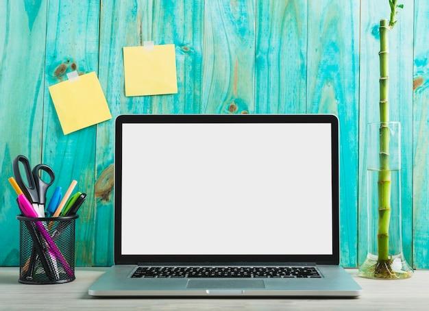 Primer plano de la computadora portátil con papelería y planta de bambú en el escritorio de madera