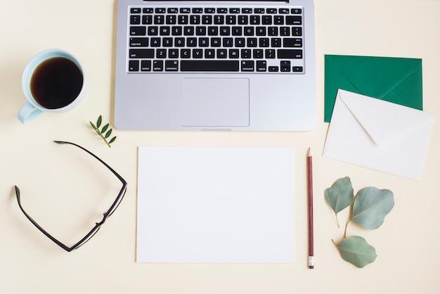 Primer plano de la computadora portátil con sobre; papel; lápiz; los anteojos; taza de té y gafas sobre fondo coloreado