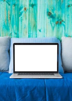 Primer plano de una computadora portátil en el sofá frente a la pared de madera de color turquesa