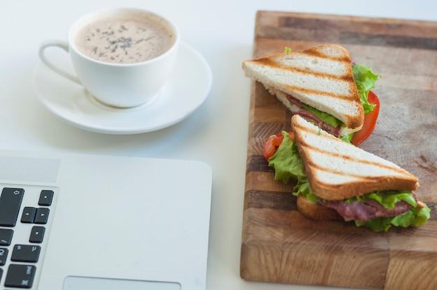 Primer plano de la computadora portátil; taza de café y sándwiches en tabla de cortar contra el fondo blanco
