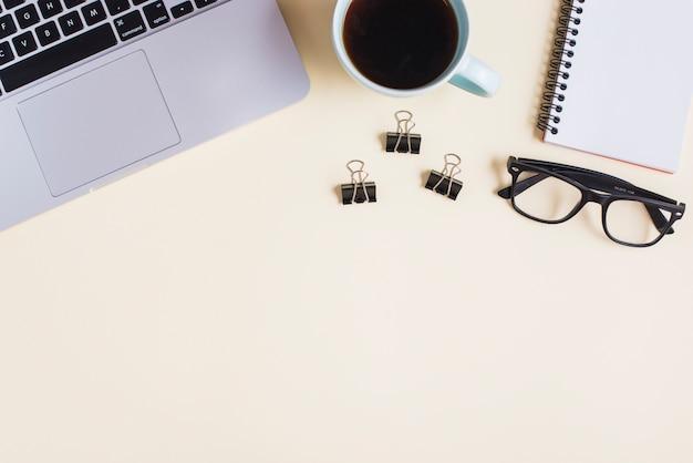 Primer plano de la computadora portátil; taza de té clip de papel; anteojos y libreta espiral sobre fondo beige