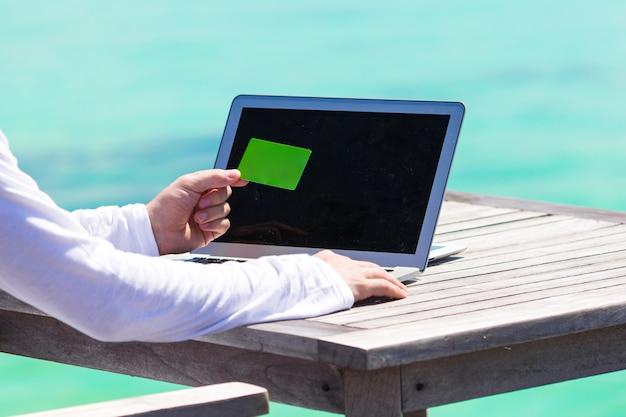 Primer plano de computadora y tarjeta de crédito en la mesa