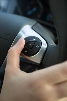 Primer plano del conductor mediante el panel de control en el volante