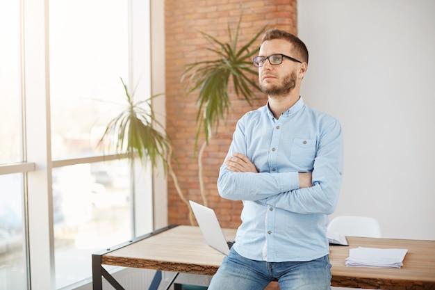 Primer plano de un confiado director masculino de la compañía, posando para un artículo en una revista sobre las personas más exitosas del año