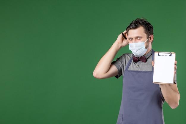 Primer plano de confuso camarero masculino en uniforme con máscara médica y sosteniendo el libro de pedidos sobre fondo verde