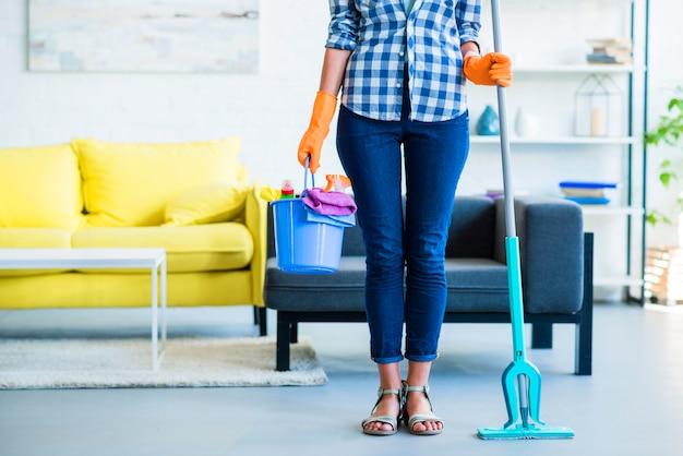 Primer plano de conserje femenino sosteniendo equipos de limpieza en casa
