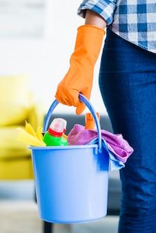 Primer plano de conserje femenino sosteniendo equipos de limpieza en el cubo azul