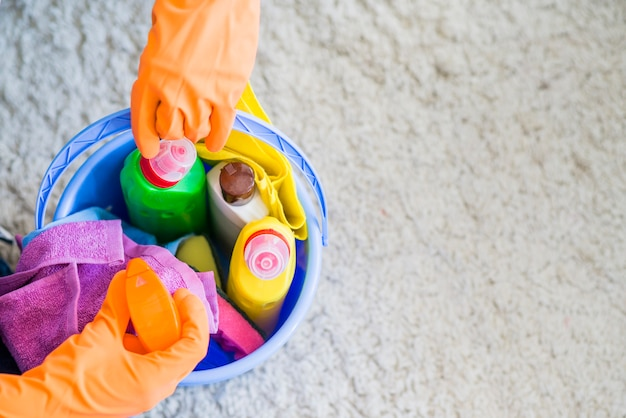 Primer plano de conserje tomando artículos de limpieza de la cubeta