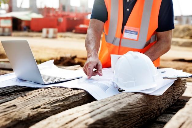 Primer plano de contratista en sitio de construcción apuntando al plan en durmiente de madera