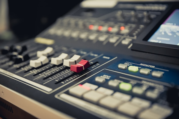 Primer plano de un control deslizante de volumen en el mezclador de sonido profesional.