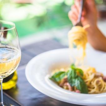 Primer plano de una copa de vino con persona comiendo espaguetis