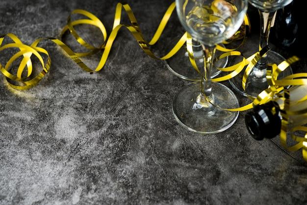 Primer plano de copas de vino vacías transparentes y botella con serpentinas doradas sobre fondo texturizado