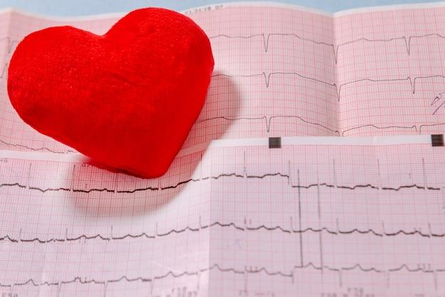 Primer plano de corazón rojo en el electrocardiograma (ecg). cardiología, salud y concepto médico.