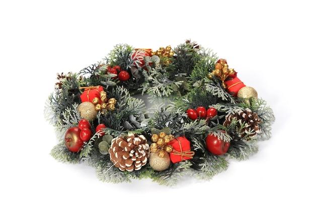 Primer plano de una corona bellamente decorada con piñas, pequeños regalos sobre un fondo blanco.