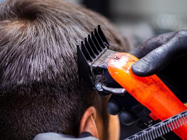Primer plano de corte de pelo naranja trimmer