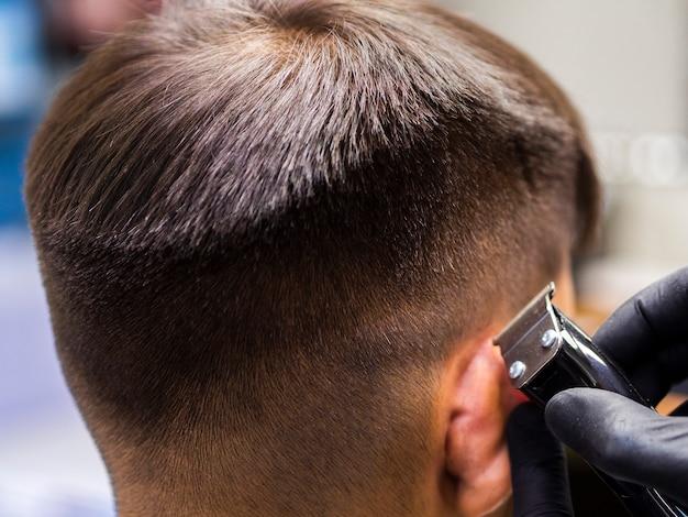 Primer plano de corte de pelo y recortadora de lado