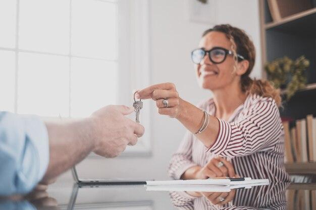El primer plano de la cosecha del agente inmobiliario le da las llaves al comprador o al arrendatario que compra la primera casa de la agencia.
