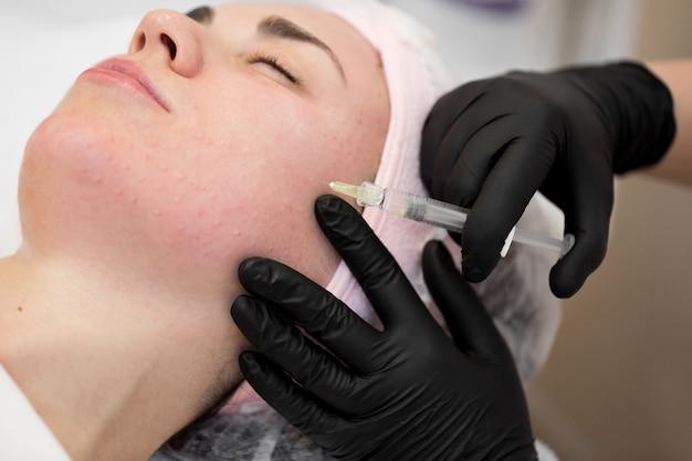 El primer plano de la cosmetóloga realiza el procedimiento de inyecciones faciales rejuvenecedoras para tensar la piel de la cara de la mujer en una clínica de belleza.