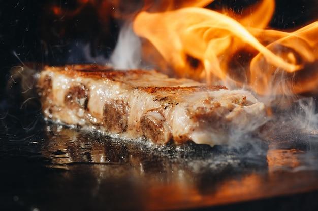 Primer plano de costillas de cerdo asadas a la barbacoa para asar a la barbacoa en la parrilla con llamas calientes