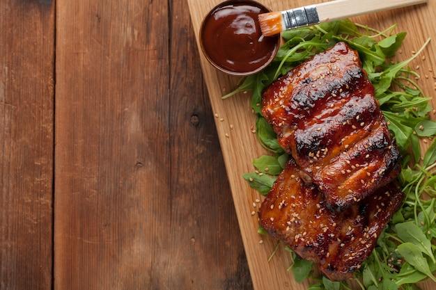 Primer plano de costillas de cerdo a la parrilla con salsa bbq.