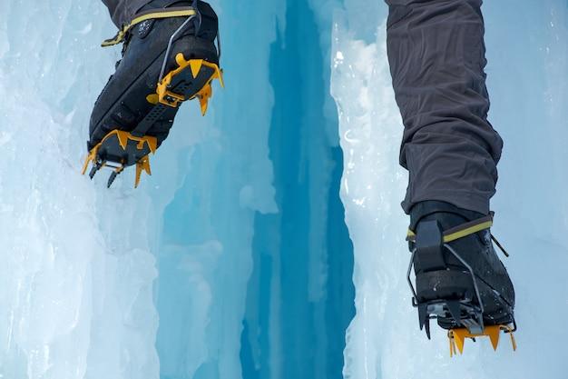 Primer plano de crampones en sus pies escalador de hielo, escalador en un invierno helado