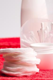 Primer plano de crema facial y almohadillas de algodón - cosméticos