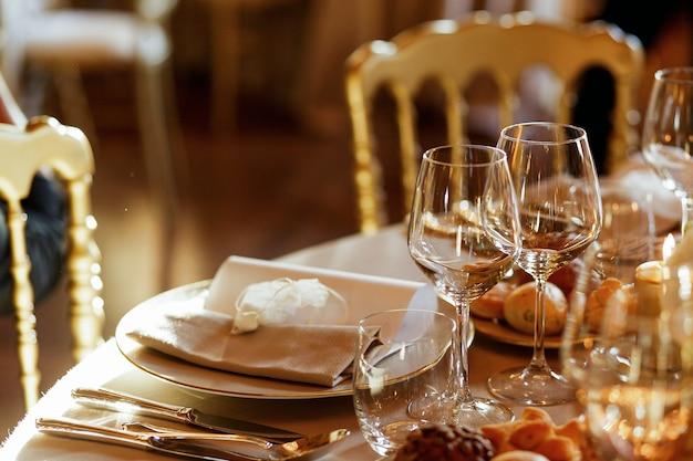 Primer plano de cristalería brillante de pie detrás de la placa de la cena