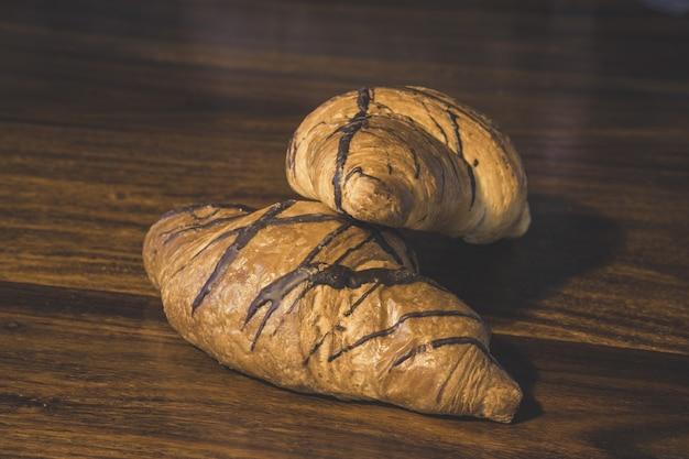 Primer plano de croissants de chocolate sobre una superficie de madera