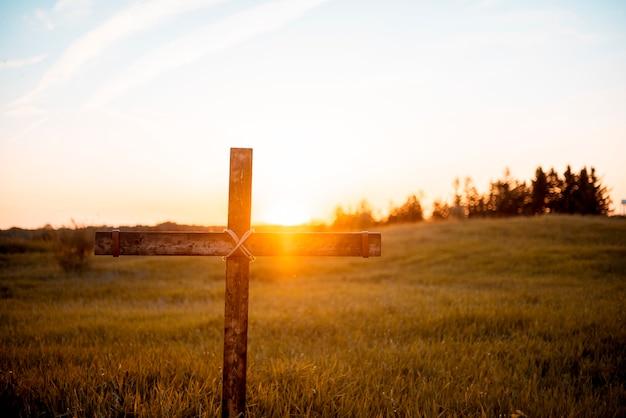 Un primer plano de una cruz de madera artesanal en el campo con el sol brillando