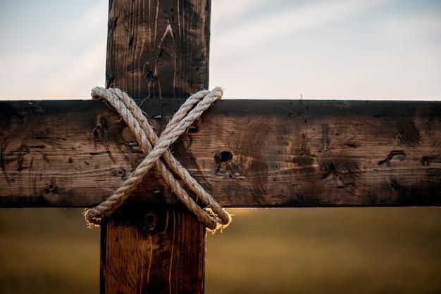 Primer plano de una cruz de madera con una cuerda envuelta y un fondo borroso