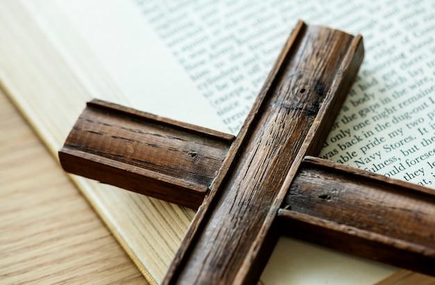 Primer plano de una cruz de madera en el libro de la biblia