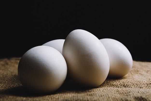Primer plano de cuatro huevos blancos sobre una superficie marrón sobre una pared negra
