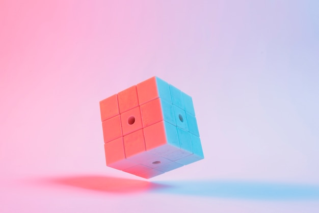Primer plano del cubo del rompecabezas 3d en fondo rosado