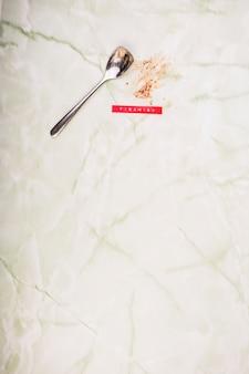 Primer plano de cuchara y postre de tiramisú comido en mármol